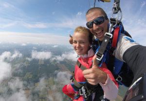 Exemple de photo en vol prise par l'instructeur tandem sous le parachute ouvert représentant une cliente heureuse qui fait un thumb up.