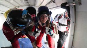 Une élève parachutiste prend position dans la porte de l'avion pour son premier saut autonome accompagnée de deux instructeurs.